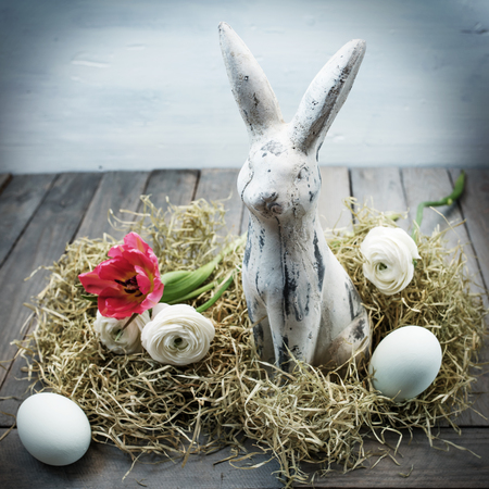 eastertime: Easter nest with eggs and a bunny in shabby chic style on a wooden table Stock Photo