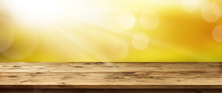 Spring background panorama with golden sunrise and empty wooden table for a concept