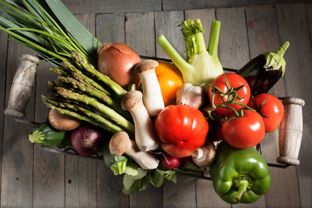 close up of onions in a basket: Assortment of fresh vegetables in a basket on a rustic wooden table