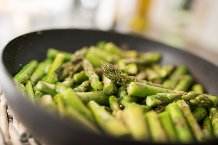 Fried green asparagus in a pan close up Stock Photo
