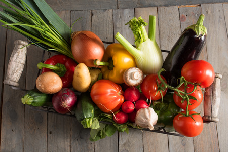 close up of onions in a basket: Colorful fresh vegetables in a basket on a old shabby wooden table Stock Photo