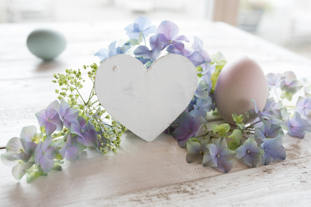 Easter still life in vintage style with flowers and a heart for love greetings