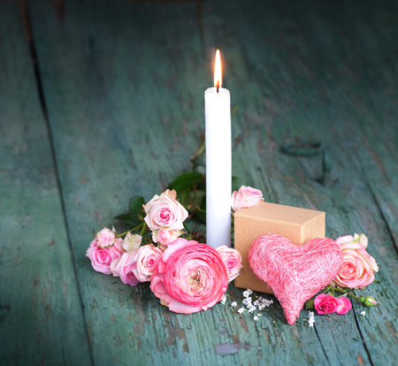Still life in pink with a candle for mothers day on an old shabby wooden table Stock Photo