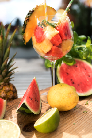 depth of field: Fresh fruits prepared in a cocktail glass on a terrace in summer