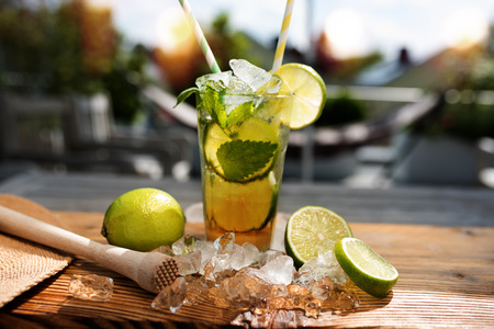 depth of field: Caipirinha with ice cube and limes on a wooden table in summer