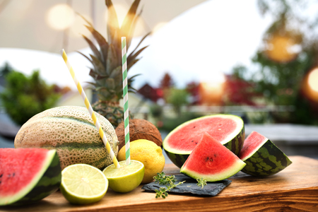 melon field: Freshly sliced melons and lemons on a wooden table in summer with bokeh Stock Photo