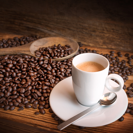Close up of cup of espresso with fresh beans on a wooden table