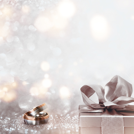 Wedding rings with a present on an abstract silver glitter bokeh background Stock Photo