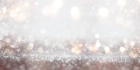 Festive glittering silver bokeh background with golden light effects for a celebratory decoration Standard-Bild