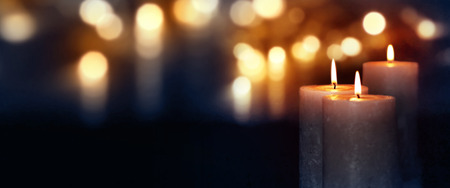 Dark blue background with burning candles and golden bokeh for a solemn occasion