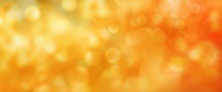 Abstracte gouden en oranje lichtgevende herfst achtergrond met bokeh effect