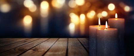Dunkelblauer Hintergrund mit goldenen Lichtern und brennenden Kerzen auf einem Holztisch für eine feierliche Zeremonie