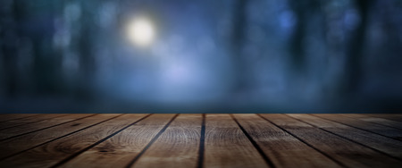 Dark mystical forest with moonlight and rustic wooden floor for a halloween concept