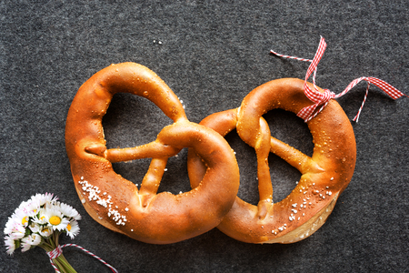 Close up of two salt pretzel with red checkered loop and daisy on a felt mat