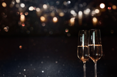 Festive dark background with golden bokeh and champagne for christmas and new year