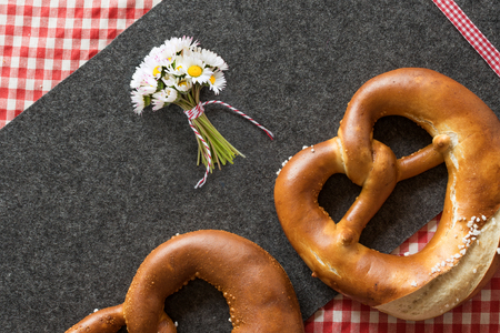 Close up of two salt pretzels with red checkered tablecloth and daisies on a felt mat