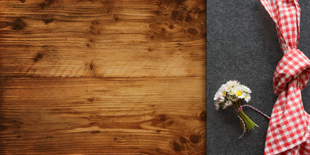 Rustic place decoration on a wooden table with red checkered napkin and daisy for a bavarian dinner