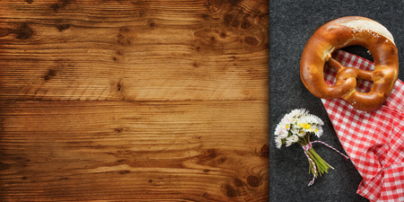 Rustic place decoration on a wooden table with pretzel and daisy for a bavarian dinner Stockfoto