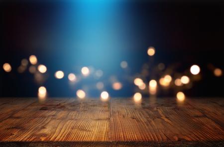 Bokeh achtergrond met blauwe lichtbundel en een lege rustieke houten tafel voor een feestelijke kerstversiering Stockfoto