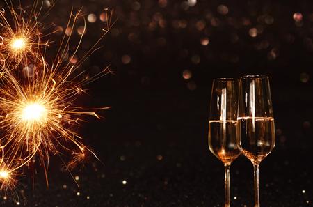 Feestelijke achtergrond met mousserende wonderkaarsen en champagne voor nieuwjaarsavond Stockfoto