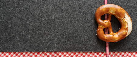 Bavarian background with red checked plaid ribbon on a felt mat and a fresh pretzel for a Oktoberfest decoration
