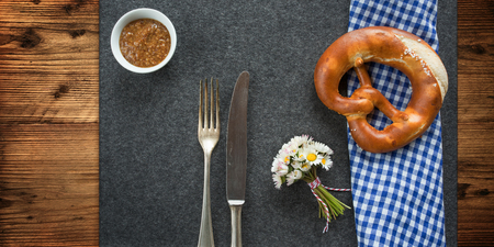 Rustic bavarian table decoration with pretzel and sweet mustard for a white sausage eating