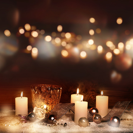 Christmas decoration in snow with burning candles and golden bokeh Banco de Imagens