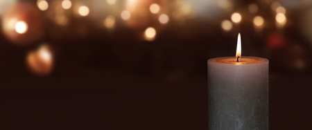 Burning candle on a dark background with golden bokeh