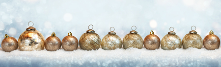 Golden christmas balls in the snow with tender bokeh Stock Photo