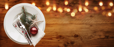 Rustic christmas table decoration on old wood with bokeh effect for a dinner