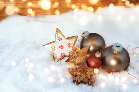 Christmas decoration in snow with silver balls and golden bokeh