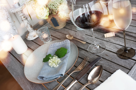 Decoration on a rustic wooden table for a romantic dinner with wine and golden bokeh