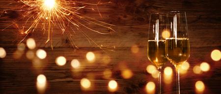 Champagne und Wunderkerze vor einer hölzernen Wand mit bokeh für eine Feier des neuen Jahres