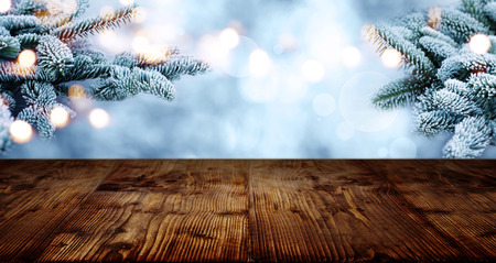 Rustic wooden table in winter with rime covered fir branches in the background