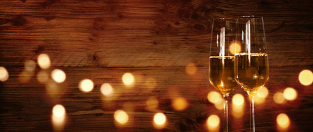 Rustic wooden wall with champagne and festive golden bokeh for a celebration Banco de Imagens