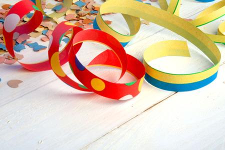 Stelle filanti colorate e coriandoli su un tavolo di legno bianco per una festa di carnevale
