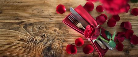 与红色玫瑰的表装饰为情人节晚餐