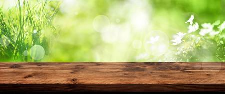 Fondo de primavera verde brillante con flores fuera de foco y mesa de madera rústica vacía para una decoración