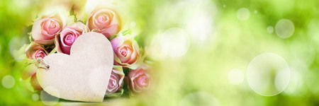 Roses with greeting card and bokeh on green spring background for mothers day Banco de Imagens