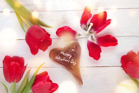 Valentines day decoration with red tulips around a described heart on white wood Stock Photo