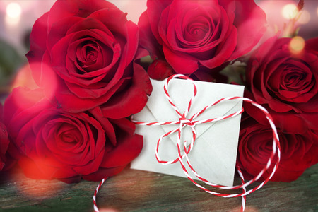 Red roses with love letter in shabby chic style and bokeh for valentines day