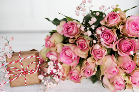 Decoration with a bouquet of pink roses and a gift on white background for mothers day