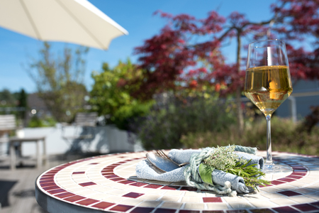 Mediterranean table decoration with herbs and a glass of white wine on a terrace
