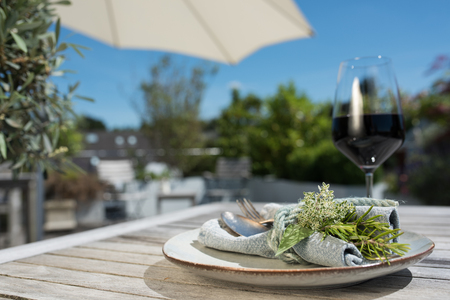 Mediterranean table decoration with a glass of red wine on a summer terrace and blue sky
