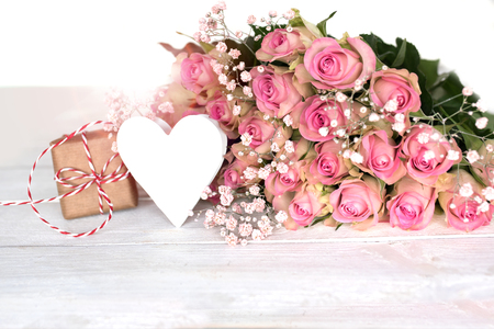 Gift and a white heart with tender pink roses on a white background for mothers day  Stock Photo