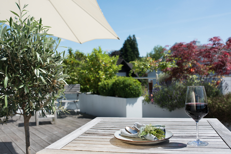 Summer on a terrace with plants and mediterranean table decoration