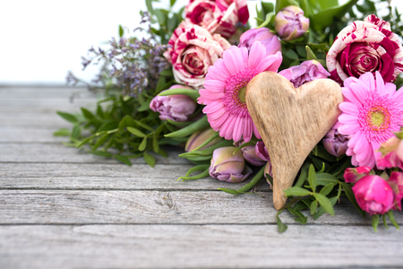 Colorful mothers day bouquet with a wooden heart on vintage planks
