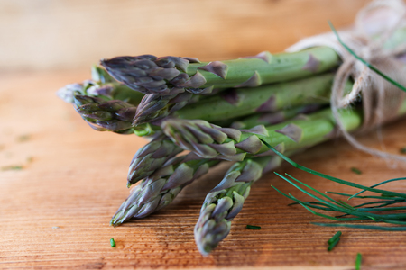 Bunch of fresh green asparagus with chives on rustic wooden table close up Banco de Imagens