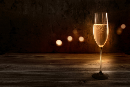 Festive background with a champagne glass on fine wood