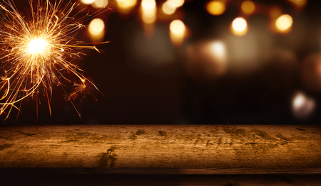 Background with sparkler and festive golden bokeh in front of empty rustic wooden table for a christmas decoration 版權商用圖片